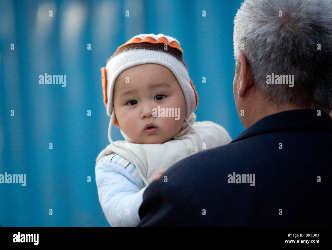 An infant looks out from over his grandfather's shoulder as they walk together down a Beijing street China. - Stock Image