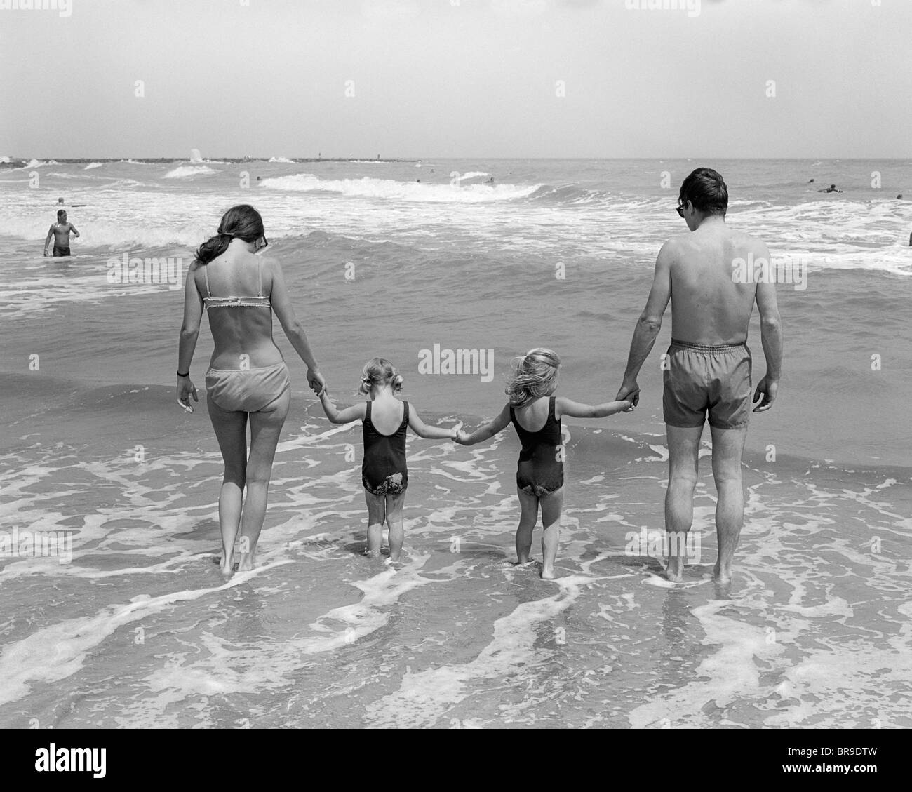 1970s FAMILY ON VACATION AT OCEAN BEACH HOLDING HANDS WALKING ON SAND IN SURF - Stock Image