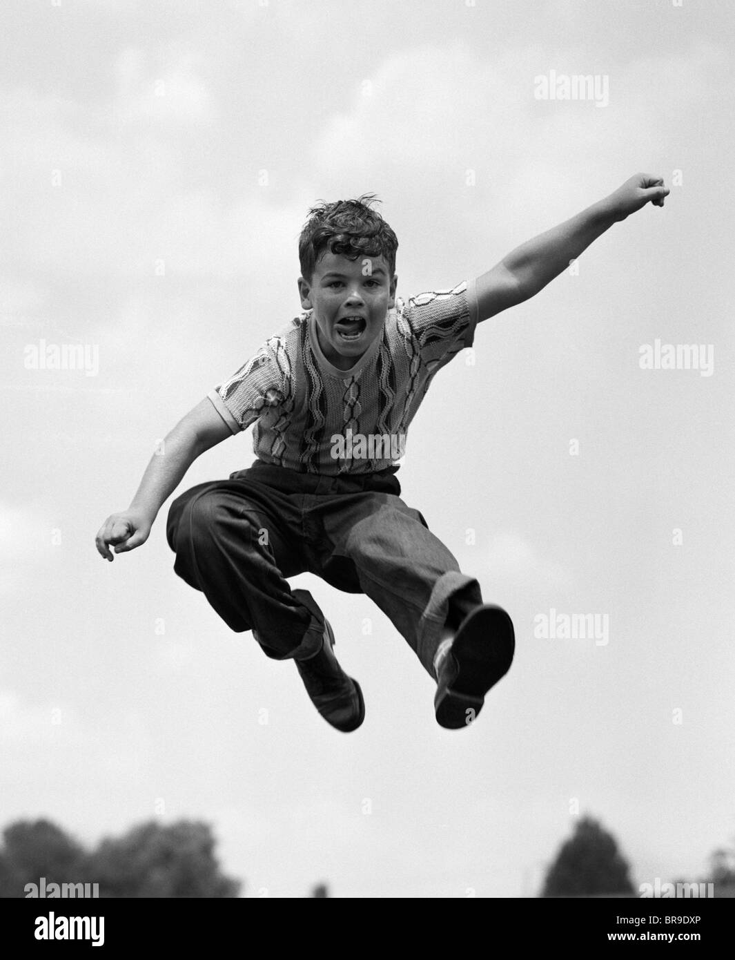 950s BOY JUMPING UP - Stock Image