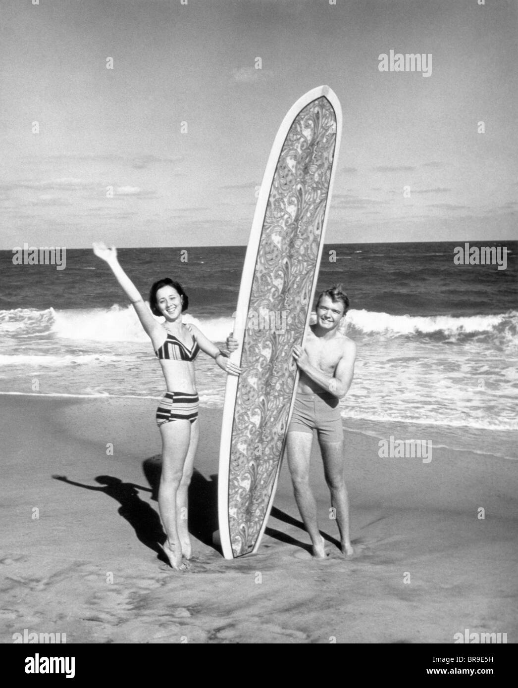 1950s COUPLE MAN WOMAN STANDING HOLDING BIG BOARD SURFBOARD ON THE BEACH LOOKING AT CAMERA - Stock Image