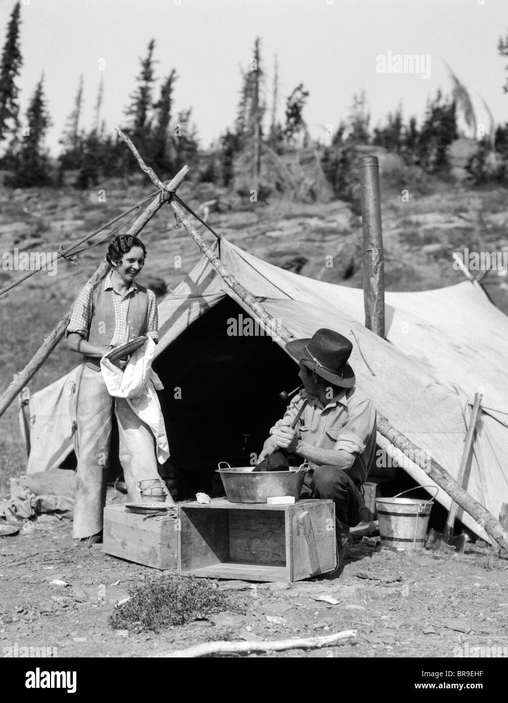 1930s SMILING TALKING COUPLE WORKING BY RUSTIC WESTERN CAMPSITE TENT MAN IN COWBOY HAT SMOKING PIPE WASHING SKILLET - Stock Image