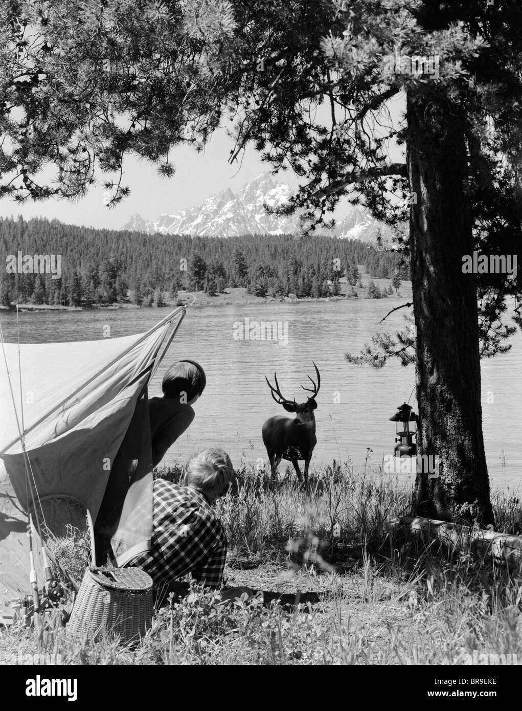 1960s CAMPERS AT GRAND TETON NATIONAL PARK WYOMING SPOTTING BUCK AT LAKESIDE - Stock Image
