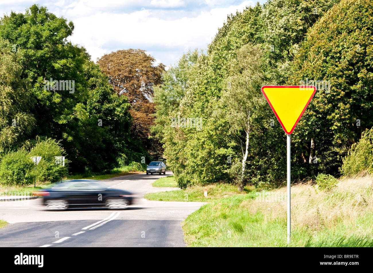 yield sign near crossroad and rushing car - Stock Image