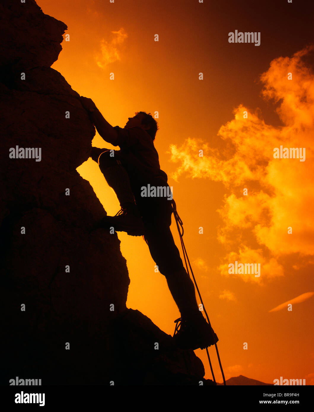 SILHOUETTE OF MAN ROCK CLIMBING AGAINST SUNSET SKY - Stock Image