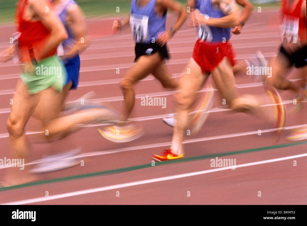 BLURRED MOTION FEET AND LEGS OF MEN RUNNING A RACE ON A TRACK - Stock Image