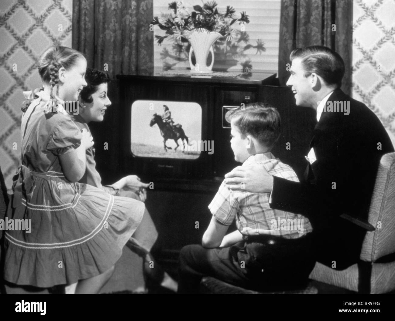 1950s FAMILY OF FOUR WATCHING BLACK AND WHITE TELEVISION PROGRAM OF A COWBOY RIDING A HORSE - Stock Image