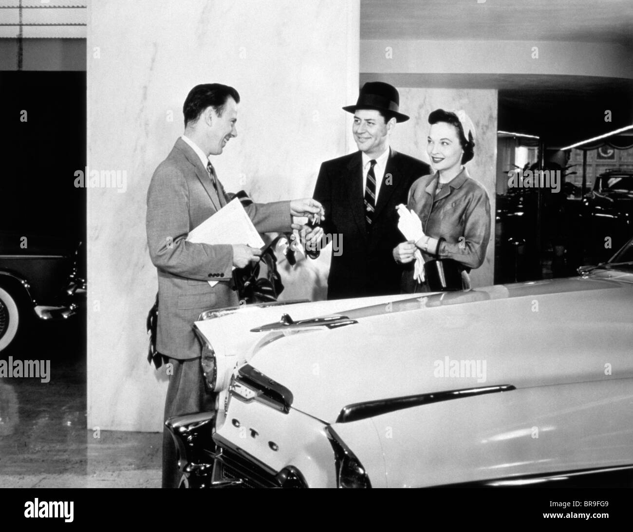1950s COUPLE BUYING NEW CAR FROM AUTOMOBILE SALESMAN HANDING OVER THE KEYS