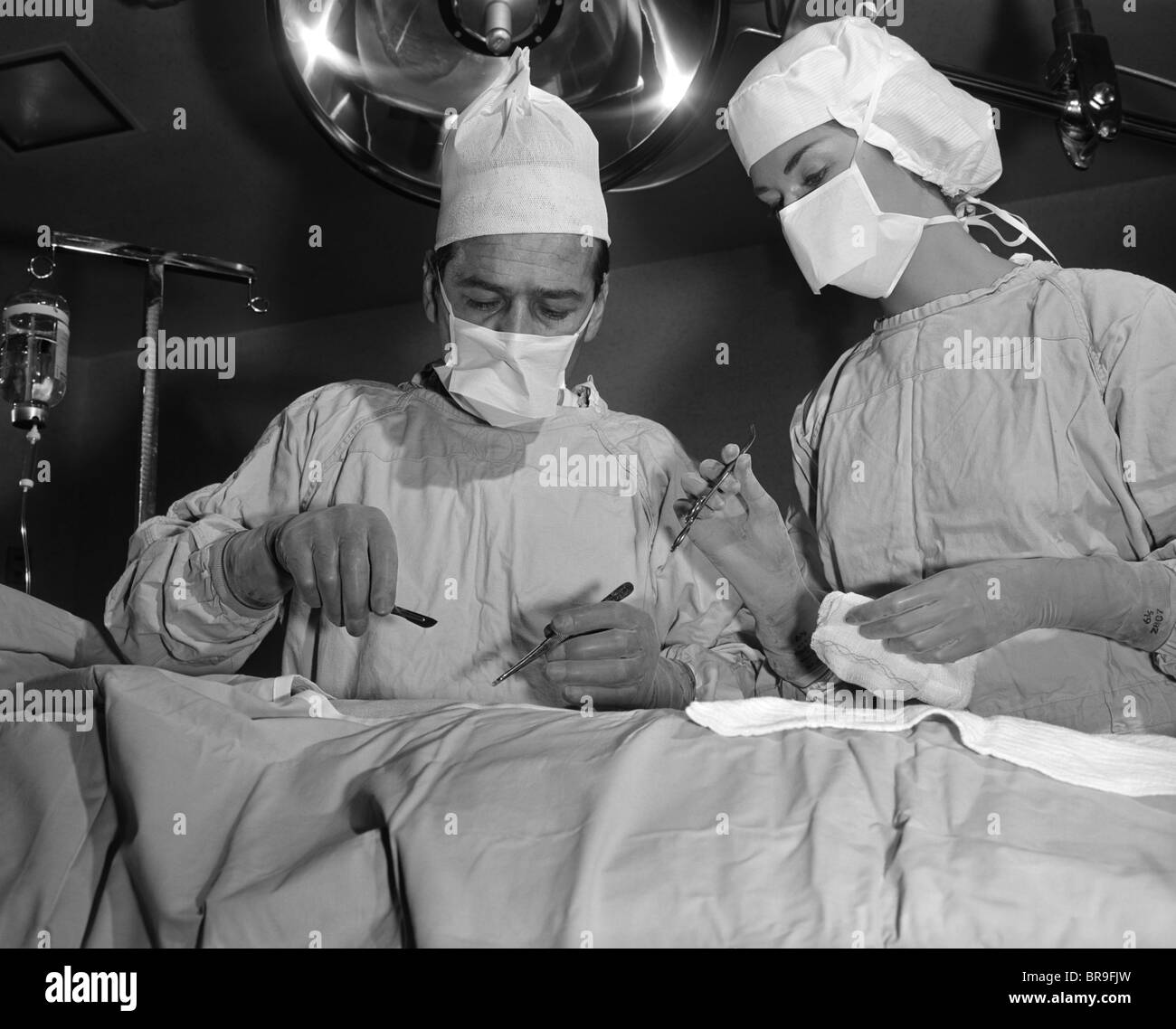 To About Nurse Standing Over 1950s Patient Operate Doctor And