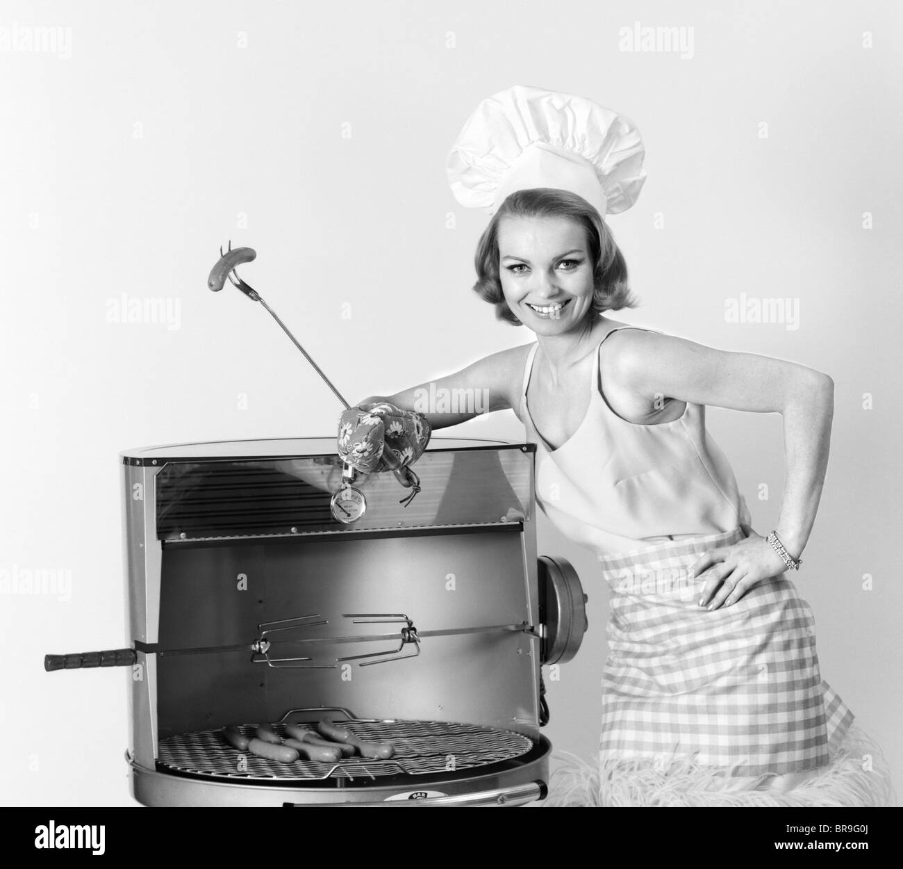 1960s WOMAN WEARING CHEF HAT STANDING AT BBQ GRILL HOLDING A FORK WITH HOT DOG - Stock Image