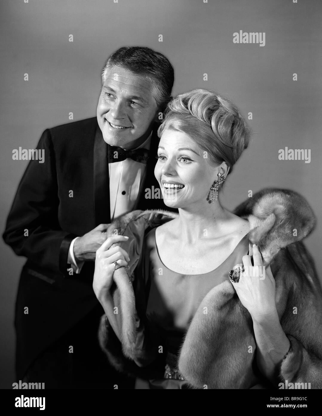 4c50aa3c4f 1960s 1970s COUPLE IN EVENING WEAR MAN IN TUXEDO WOMAN IN FUR COAT - Stock  Image