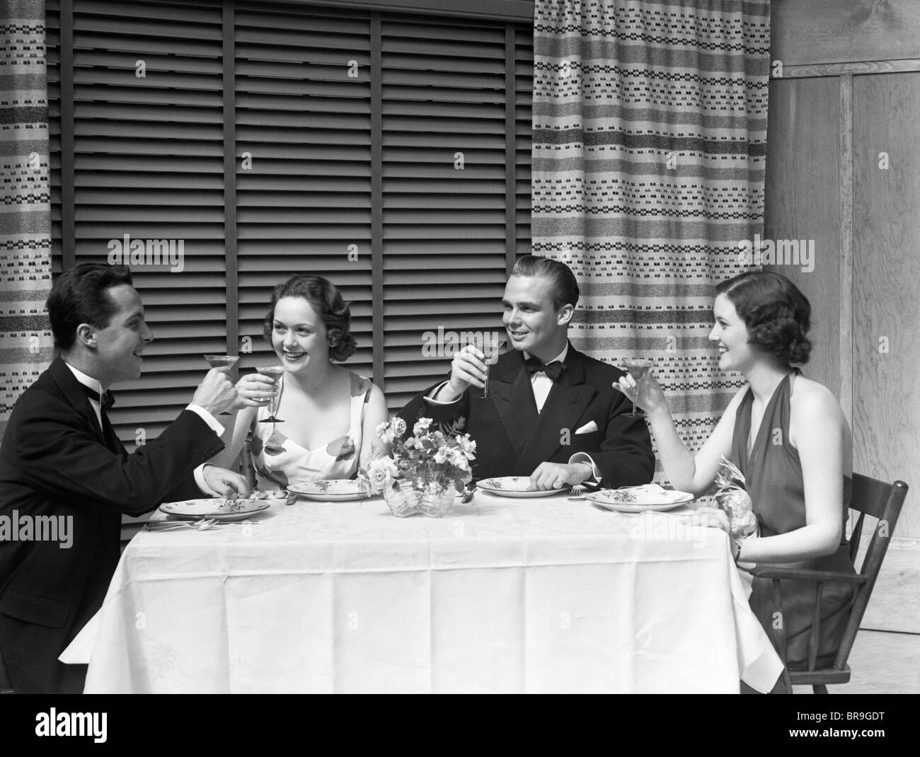 1930s DINNER PARTY TWO COUPLES IN FORMAL EVENING DRESS TOASTING - Stock Image