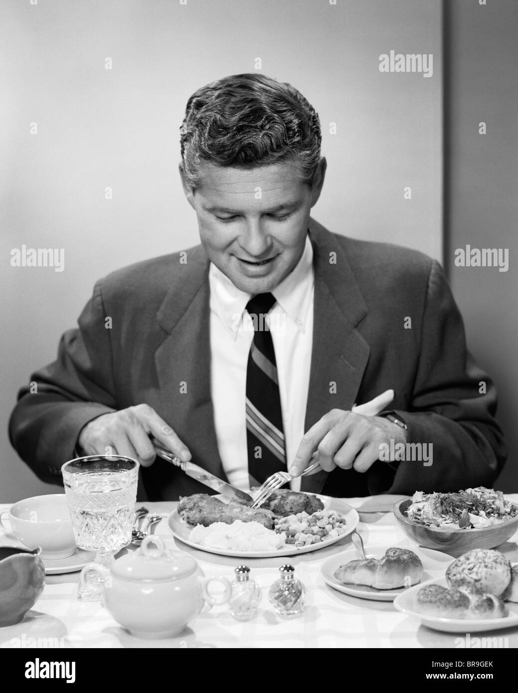 1950s SMILING MAN IN SUIT AND TIE SITTING AT TABLE HOLDING KNIFE AND FORK EATING DINNER - Stock Image