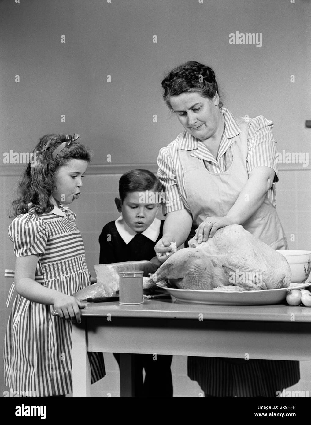 1940s MOTHER SON DAUGHTER IN KITCHEN STUFFING TURKEY FOR THANKSGIVING DINNER - Stock Image