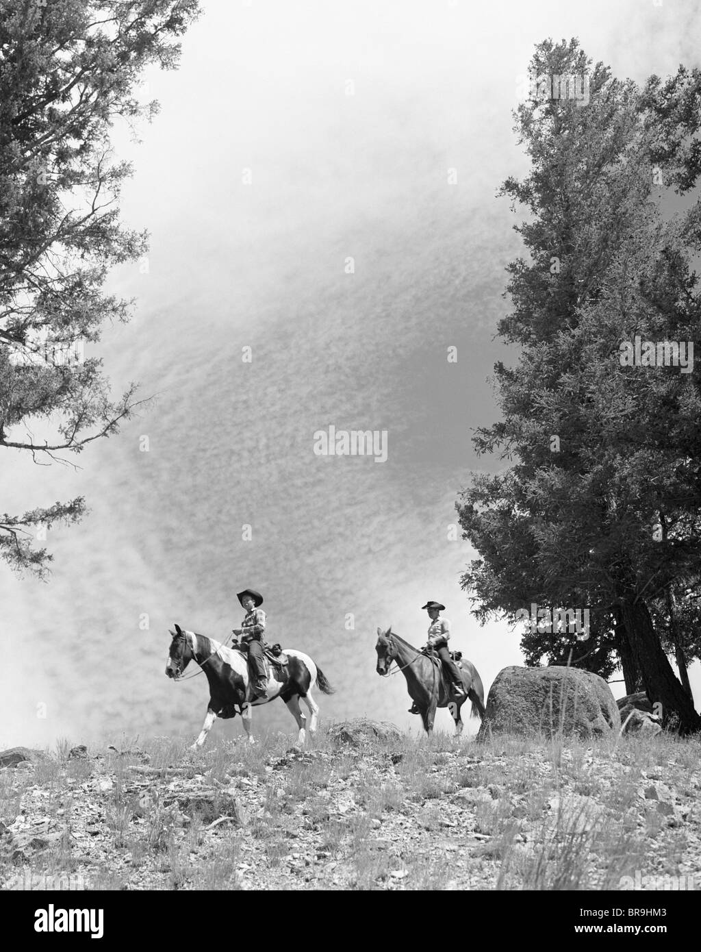 1950s 1960s TWO MEN ON HORSEBACK RIDING ACROSS FIELD WEARING COWBOY HATS - Stock Image