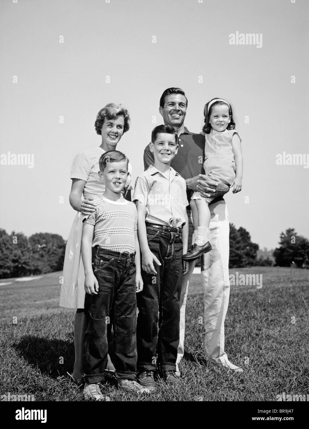 1960s SMILING FAMILY PORTRAIT STANDING ON GRASS MOTHER FATHER THREE CHILDREN - Stock Image