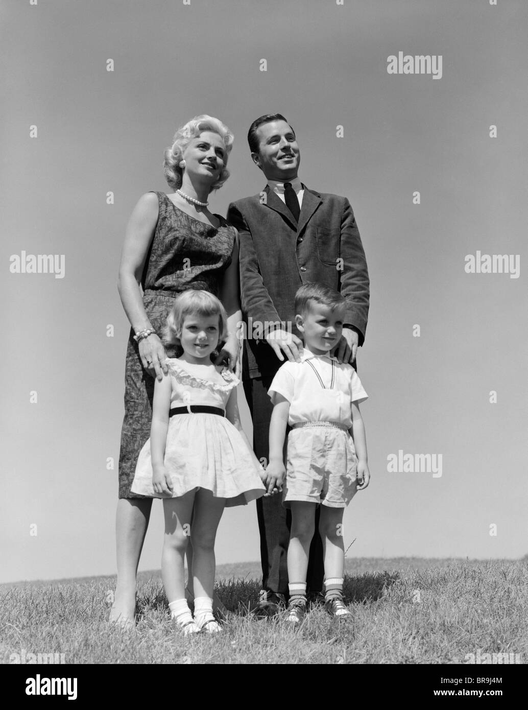 1950s 1960s PORTRAIT FAMILY STANDING IN GRASS MOTHER FATHER DAUGHTER SON - Stock Image