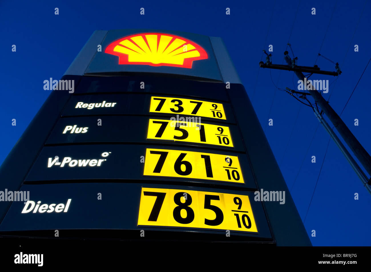 Low angle view of a gas station sign depicting 7 dollar a gallon gas near Burns Oregon. (digital composite) - Stock Image