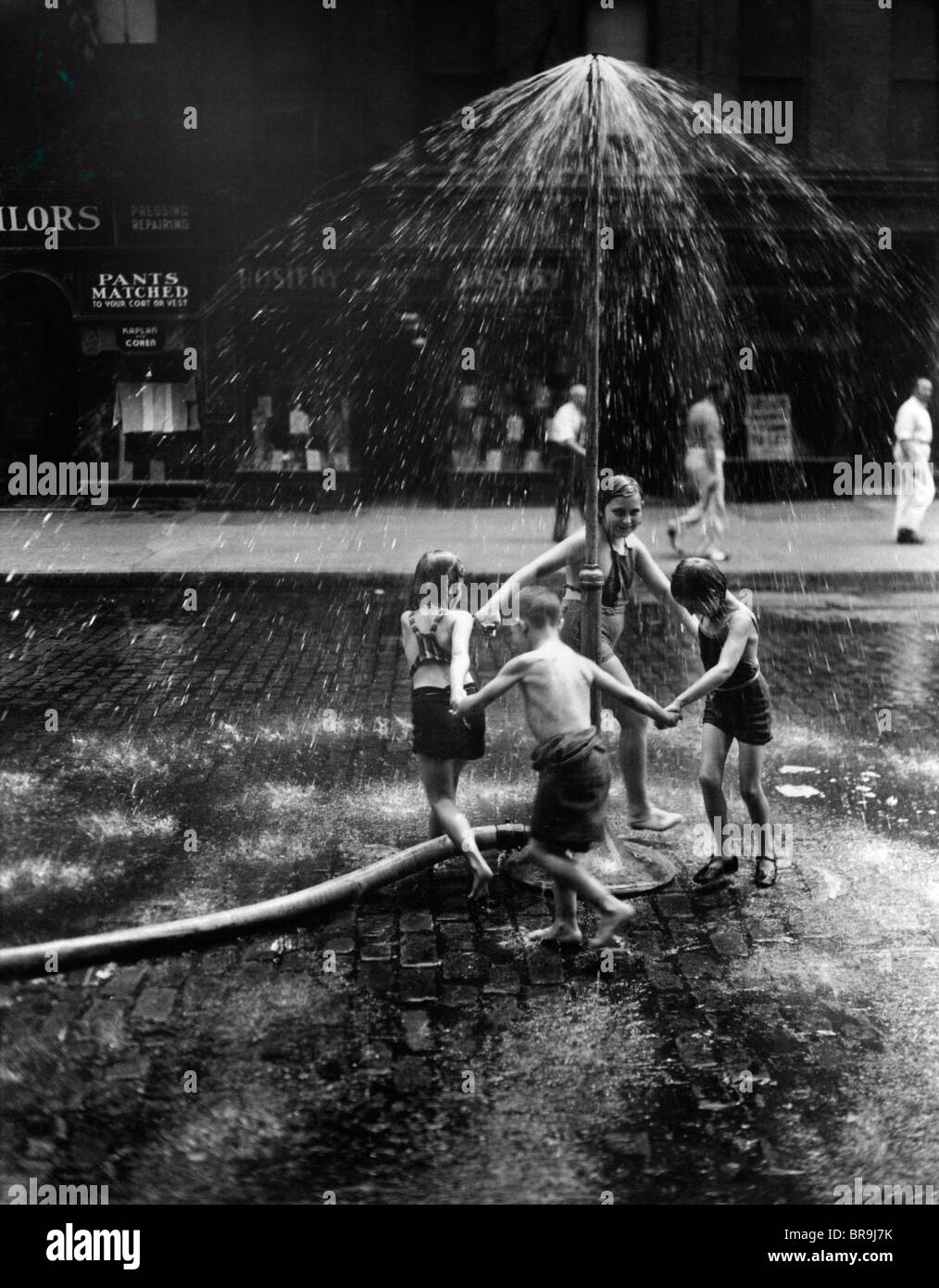 1930s INNER CITY CHILDREN PLAYING IN SPRAY FROM FIRE HYDRANT WATER SPRINKLER - Stock Image