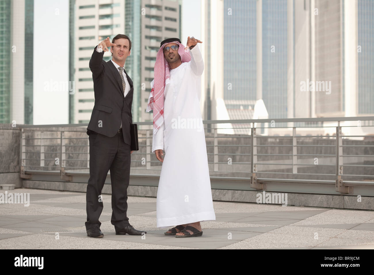 Western and middle eastern businessmen pointing - Stock Image