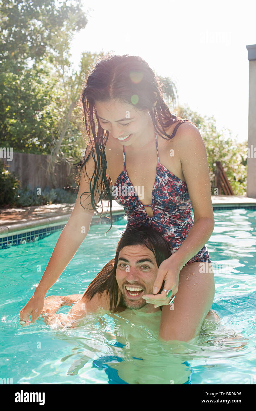 Young woman on young man's shoulders in swimming pool - Stock Image