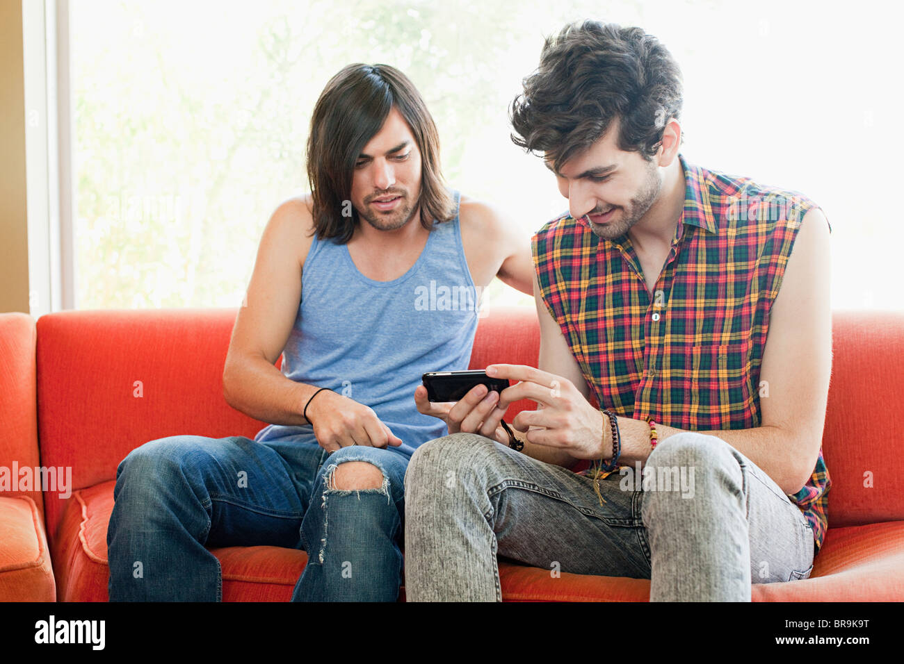 Young men on sofa with hand held device - Stock Image