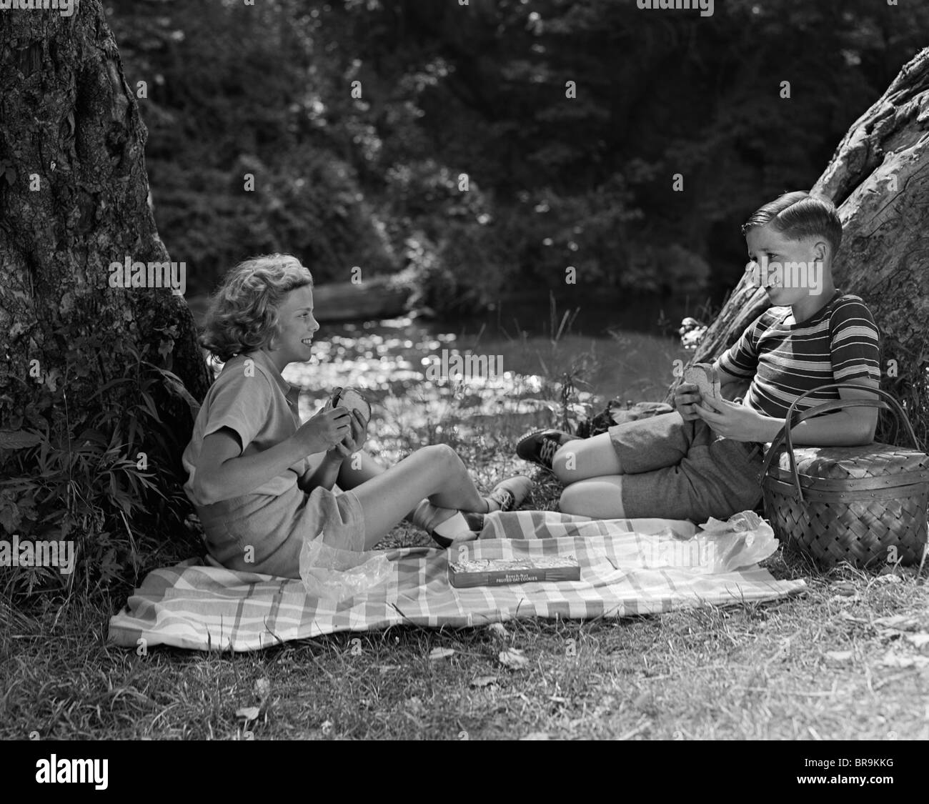 1940s BOY AND GIRL HAVING SUMMER PICNIC BY STREAM - Stock Image
