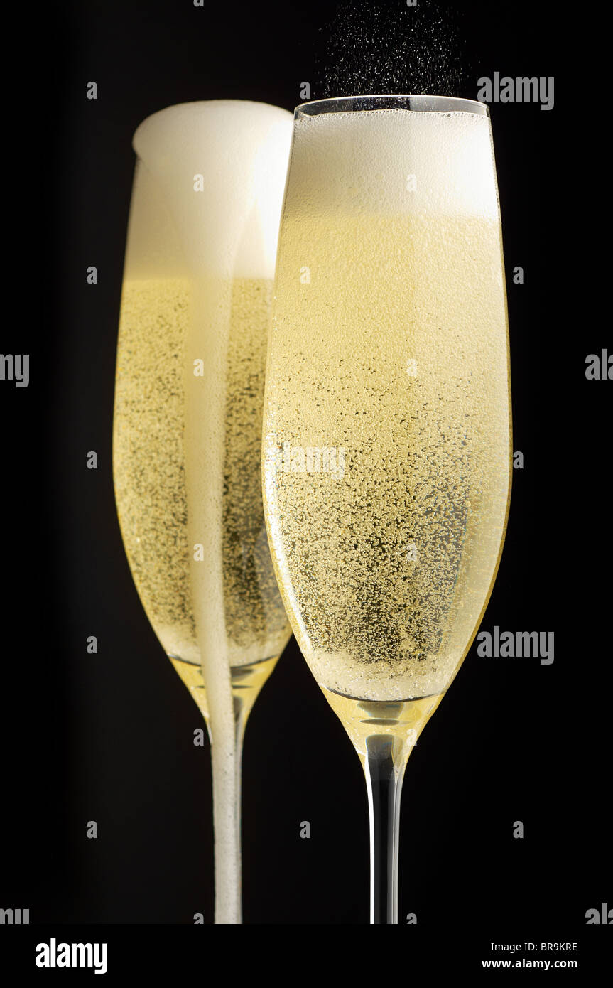 Two full champagne glasses with champagne overflowing - Stock Image