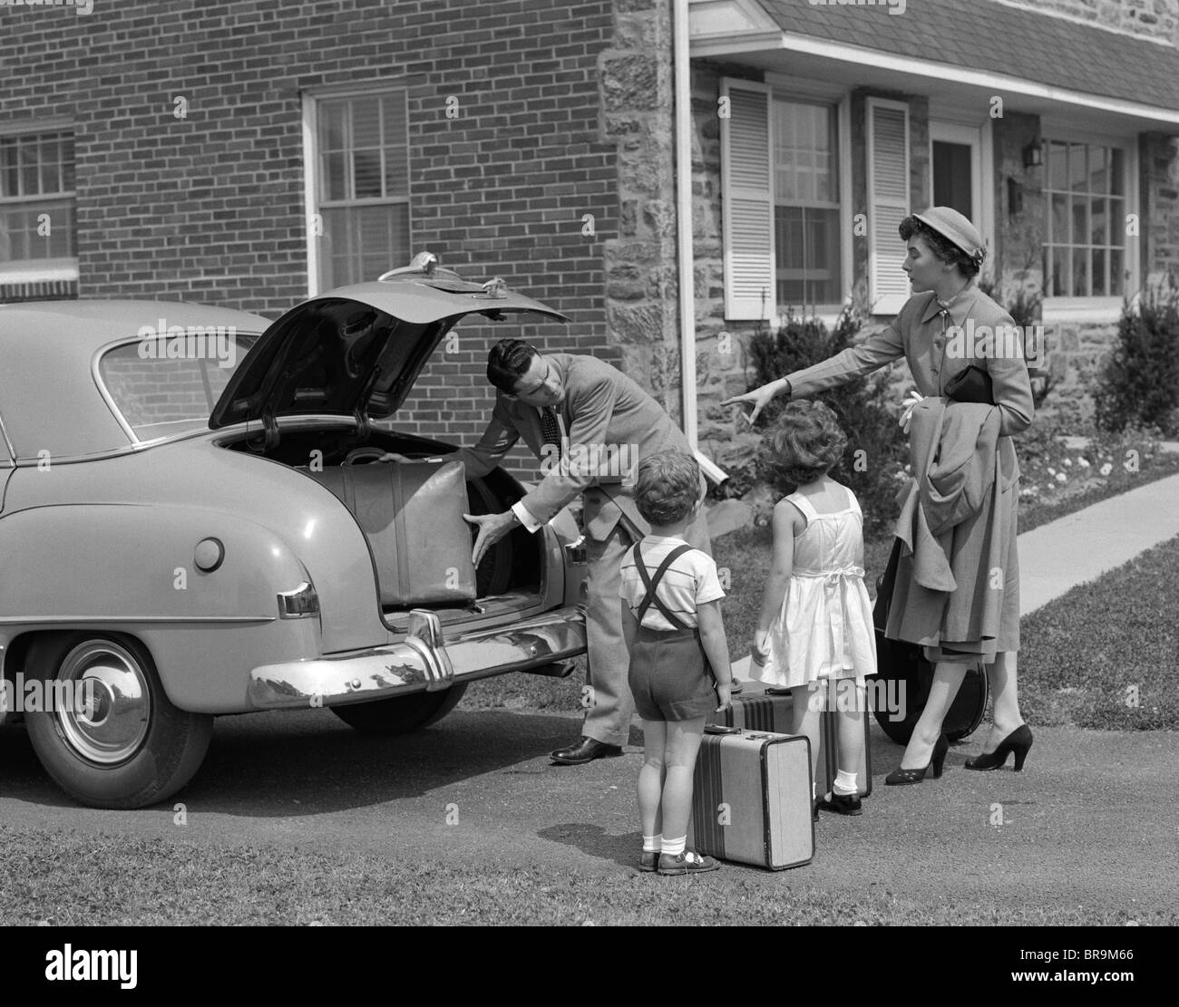 1950s FAMILY PUTTING LUGGAGE SUITCASES INTO TRUNK OF CAR - Stock Image
