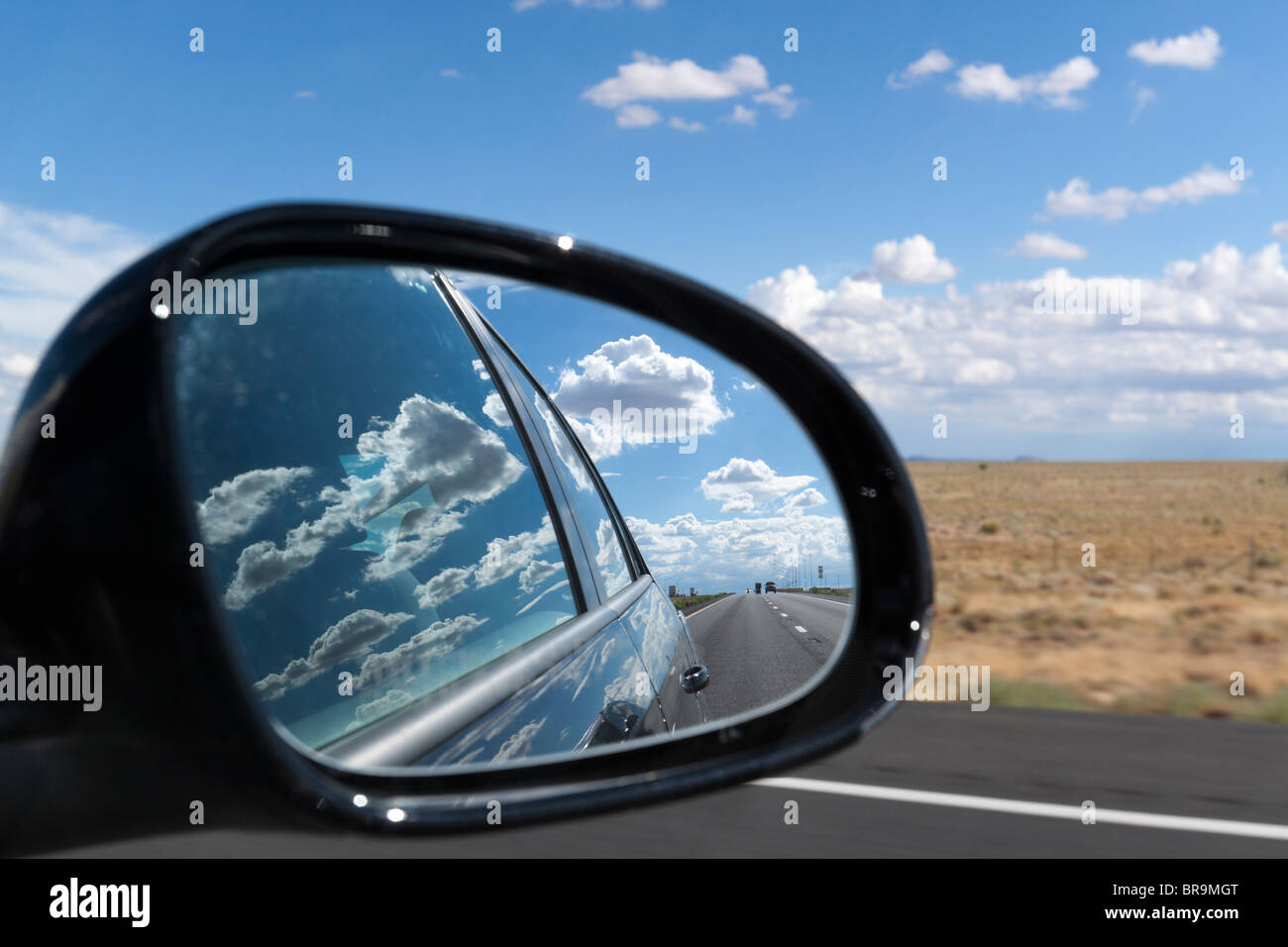 Side view mirror showing cars on the road and clouds reflecting on side of car - suggests moving on from the past - Stock Image