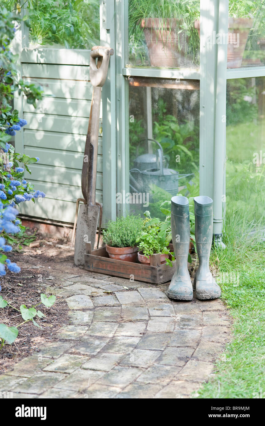Garden tools and wellington boots outside greenhouse - Stock Image