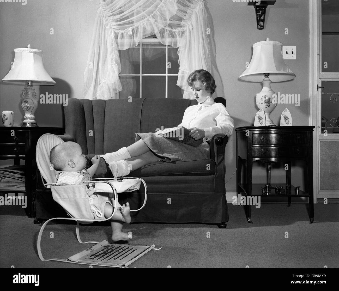 1950s TEEN BABYSITTER SEATED ON SOFA READING SCHOOLBOOK WHILE BABY ...