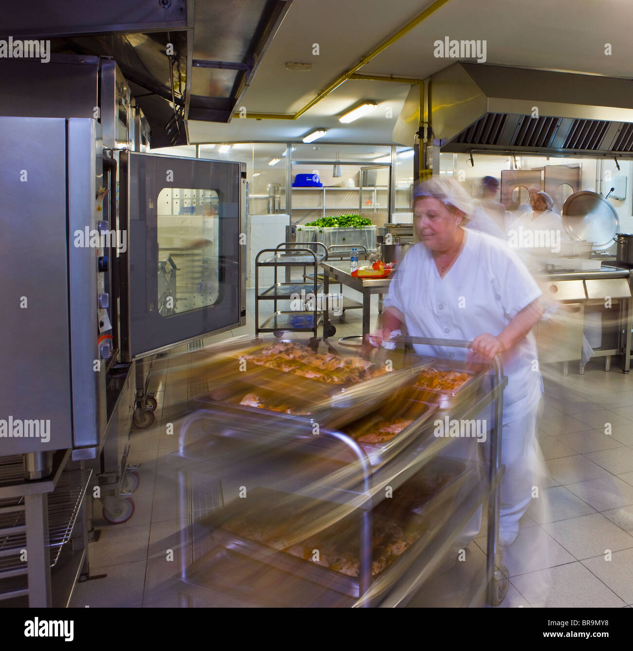 Kitchen porter pushes a trolley of pastries - Stock Image