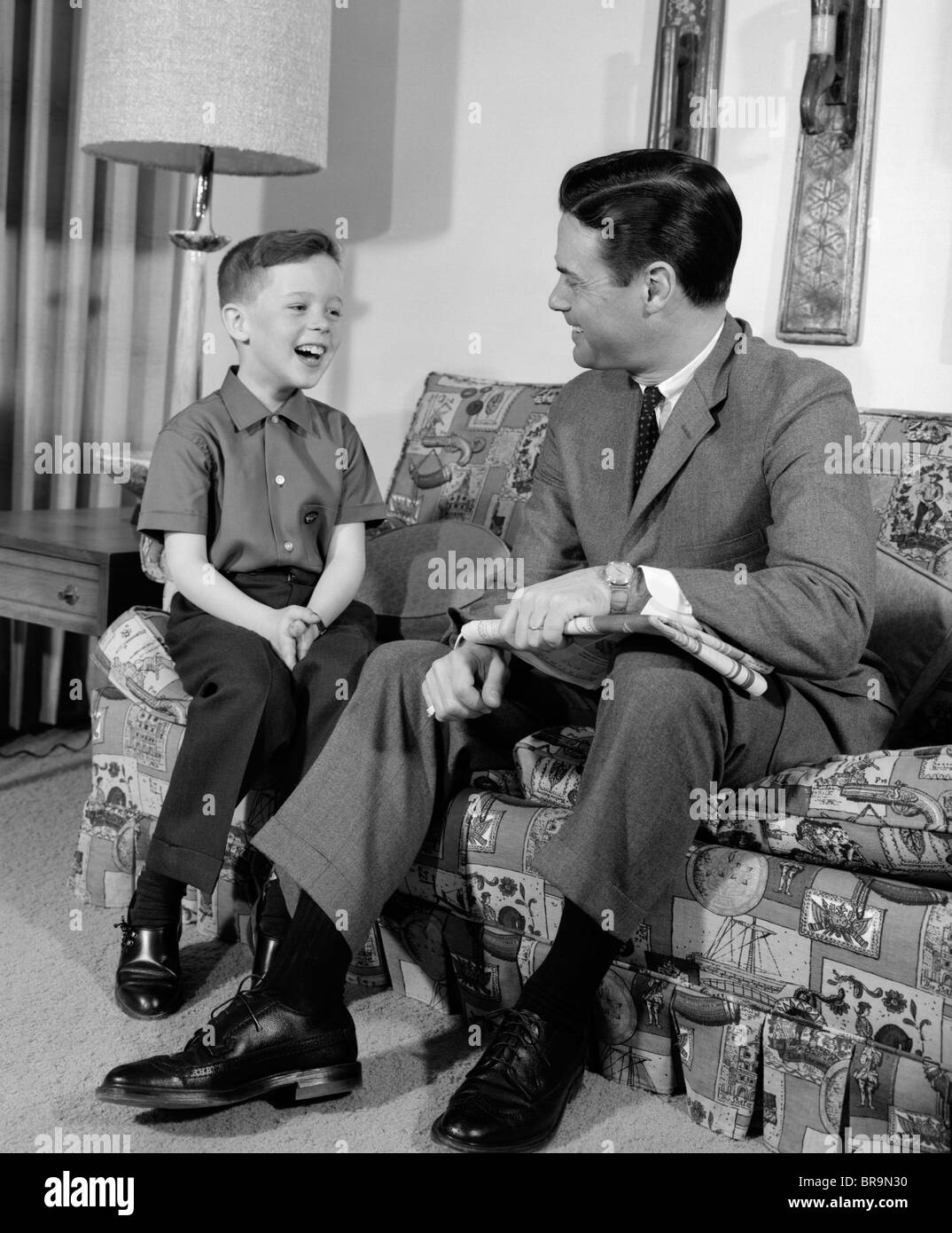 1960s BOY SITTING ON COUCH SMILING LAUGHING WITH DAD - Stock Image