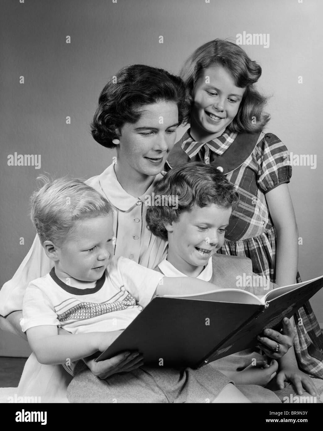 1950s MOTHER READING BOOK WITH THREE CHILDREN - Stock Image