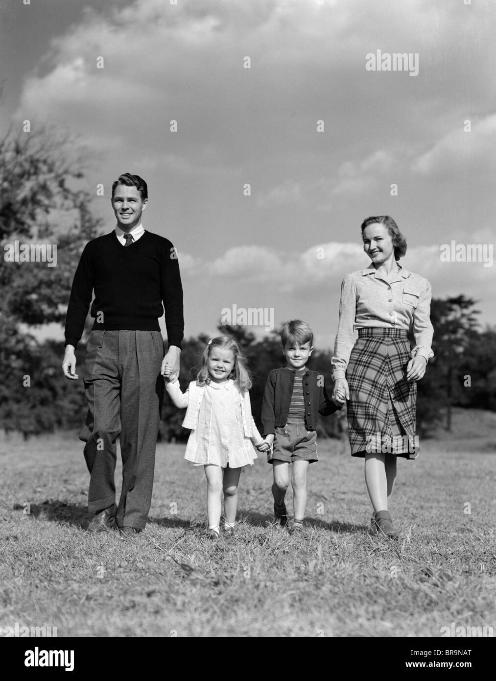 1940s FAMILY HOLDING HANDS WALKING ON GRASS - Stock Image