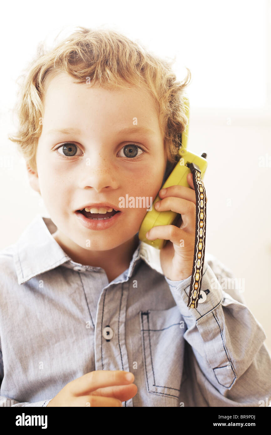 Young boy talking on a pretend cell phone - Stock Image