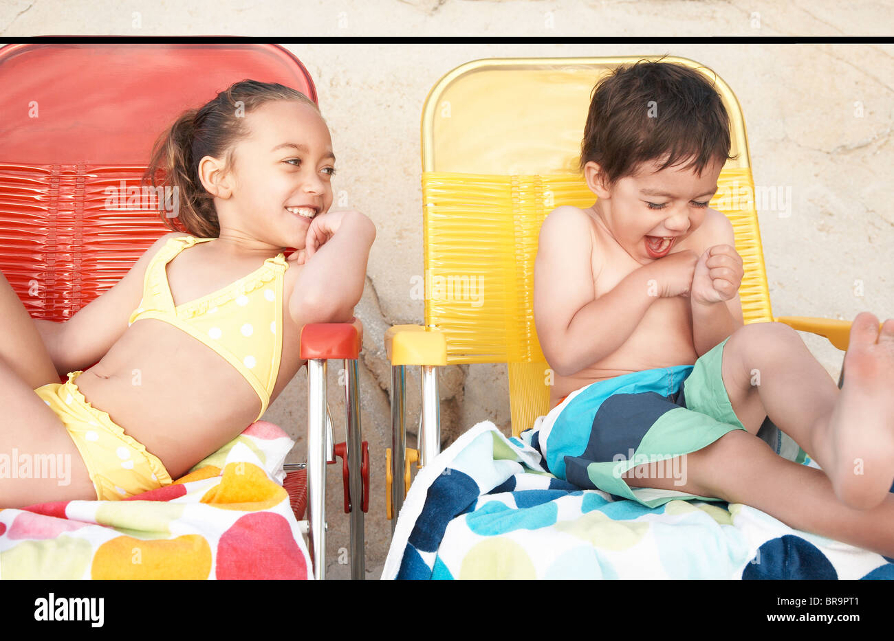 Kids in bathing suits on lounge chairs Stock Photo