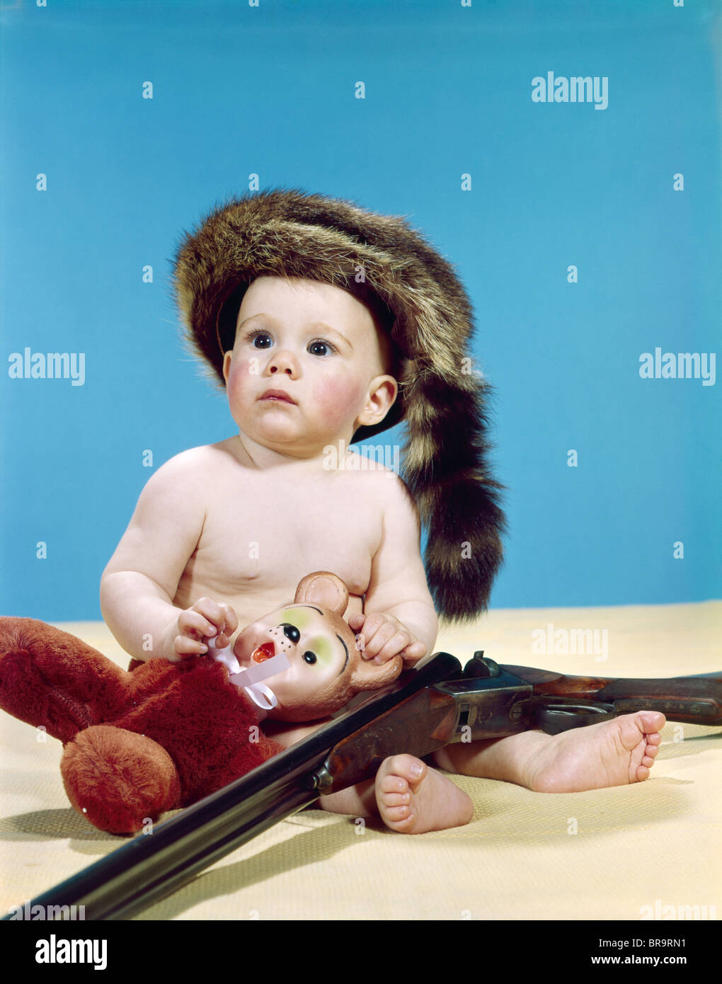 1960s BABY BOY WEARING COONSKIN CAP WITH STUFFED ANIMAL AND SHOTGUN ... ca93f64e926