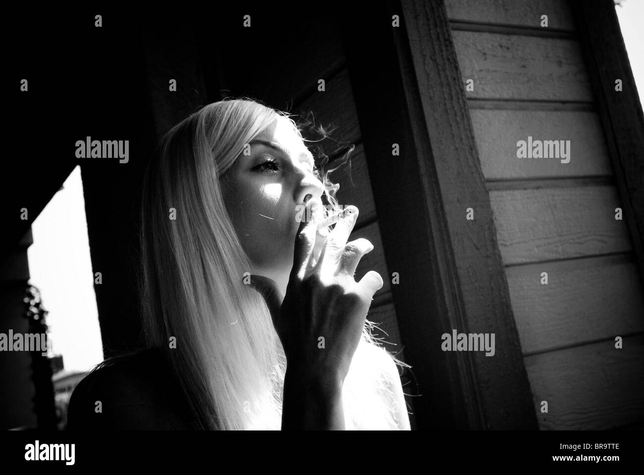 A woman smokes a cigarette. - Stock Image