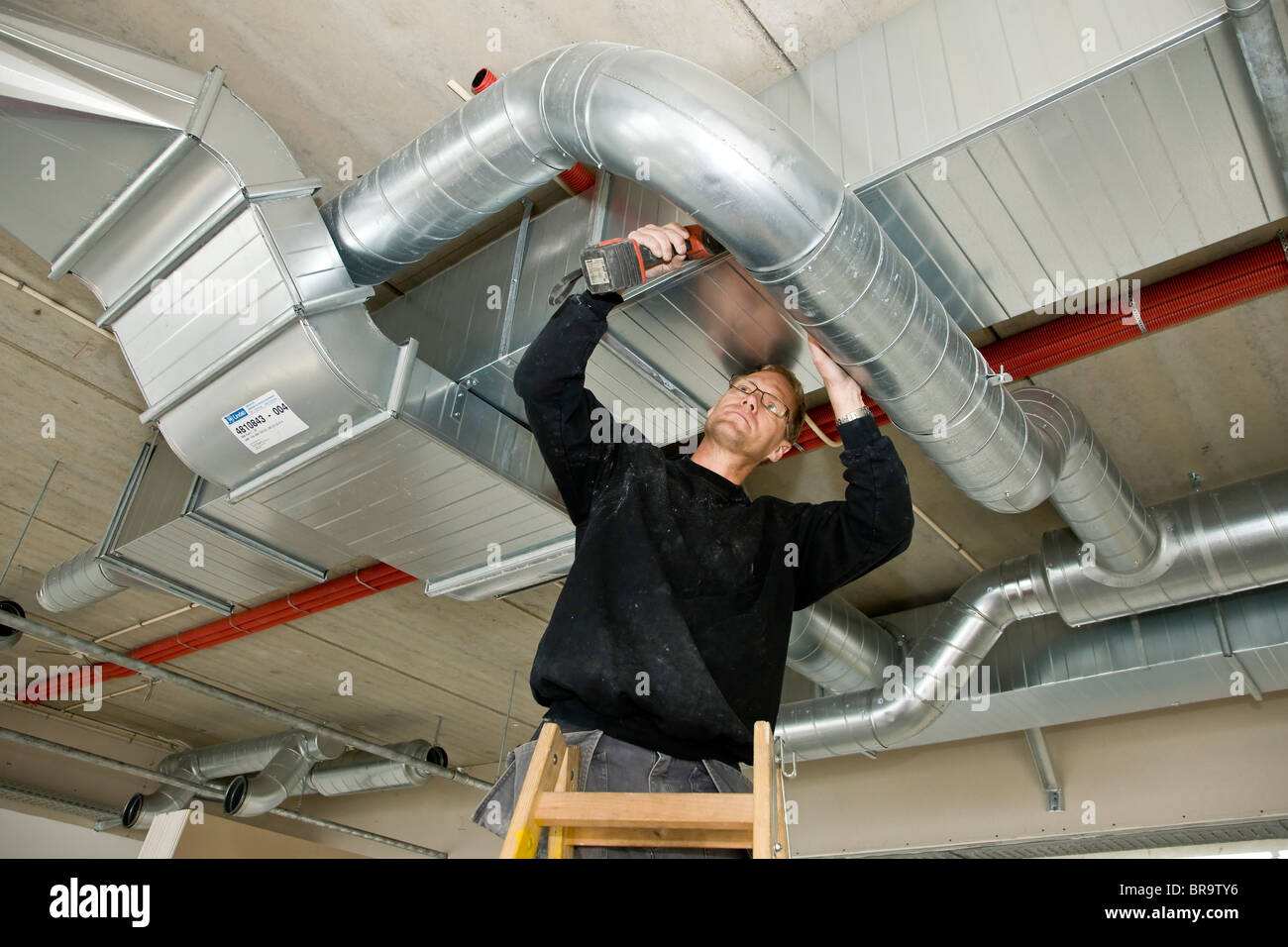 Ventilation fitter installing a ventilation pipe - Stock Image