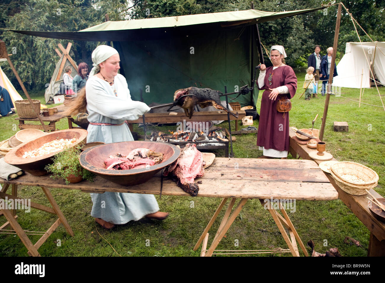 Women carry cooked deer from fire to table, Historical re-enactment Saxon, Viking, Norman history, Woodbridge, Suffolk - Stock Image