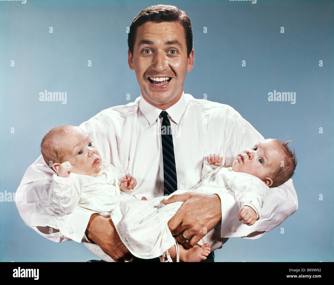 1960s SMILING MAN FATHER LOOKING AT CAMERA HOLDING TWIN BABIES INFANTS - Stock Image