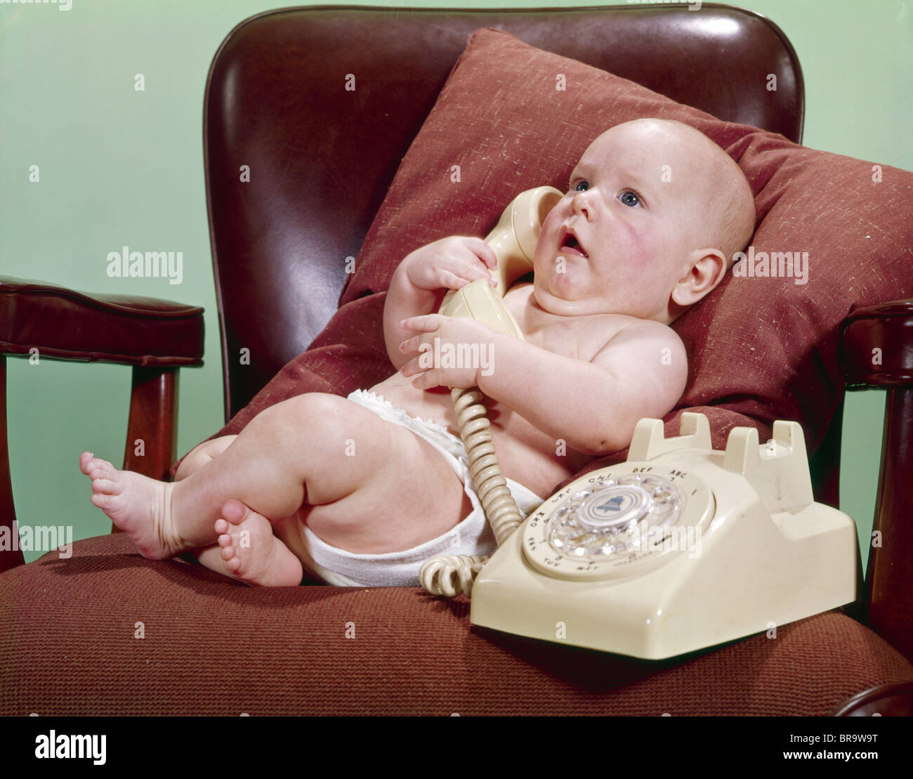 Terrific 1960S Baby In Office Chair Propped On Pillow Talking On Interior Design Ideas Apansoteloinfo