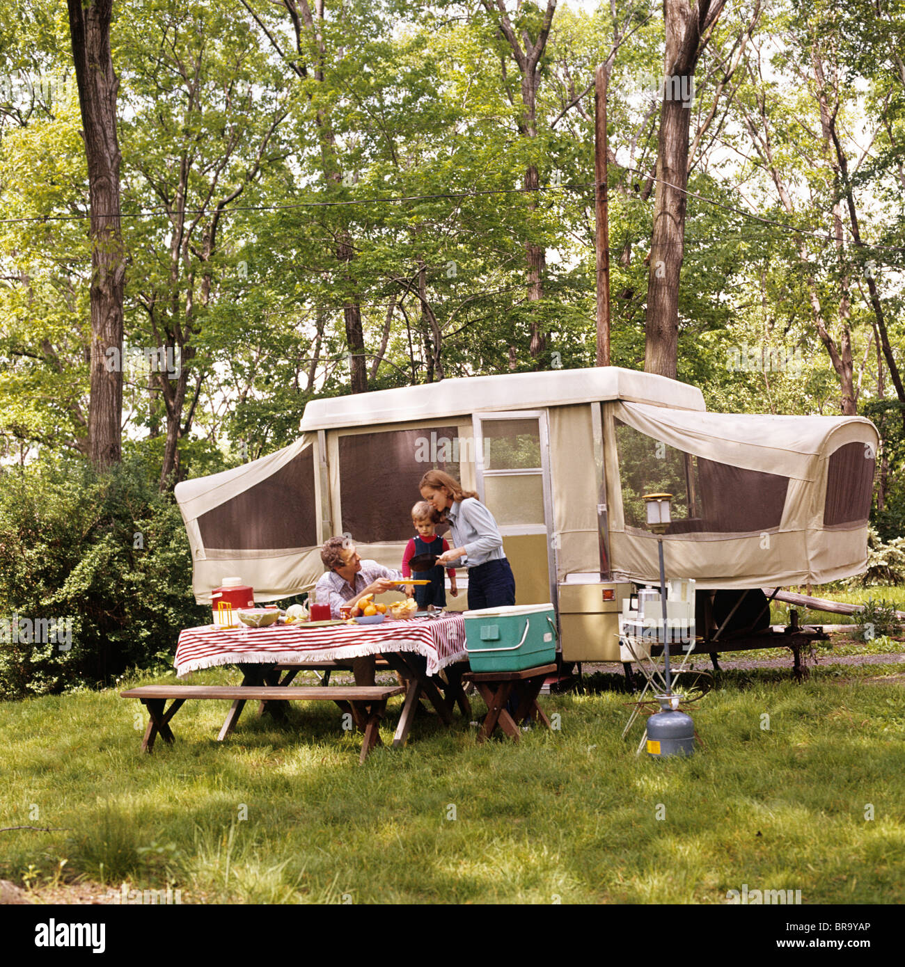 1970s FAMILY MOTHER FATHER SON CAMPING HAVING PICNIC BY CAMPER SUMMER VACATION