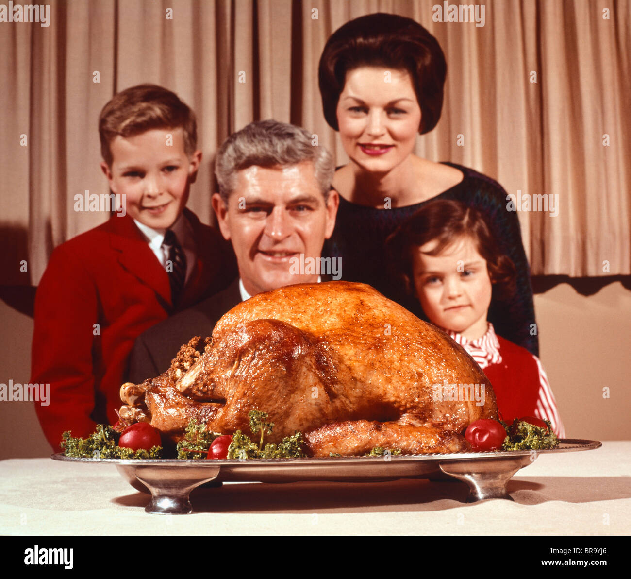 1960s PORTRAIT OF FAMILY FATHER MOTHER SON DAUGHTER LOOKING AT THANKSGIVING OR CHRISTMAS ROAST TURKEY - Stock Image