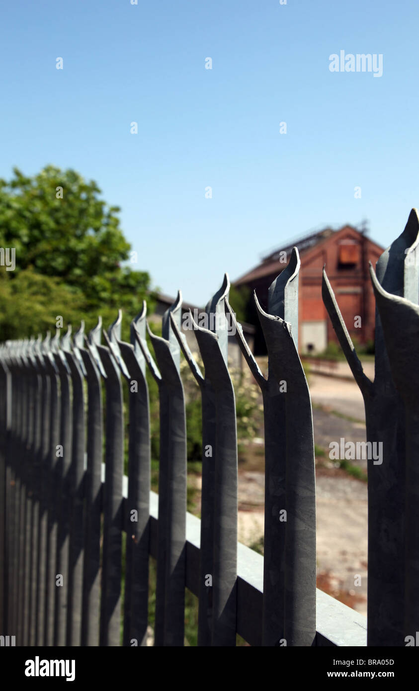 Close-up view of a barbed palisade security fence with the intention to keep out intruders. Shallow depth of field. - Stock Image