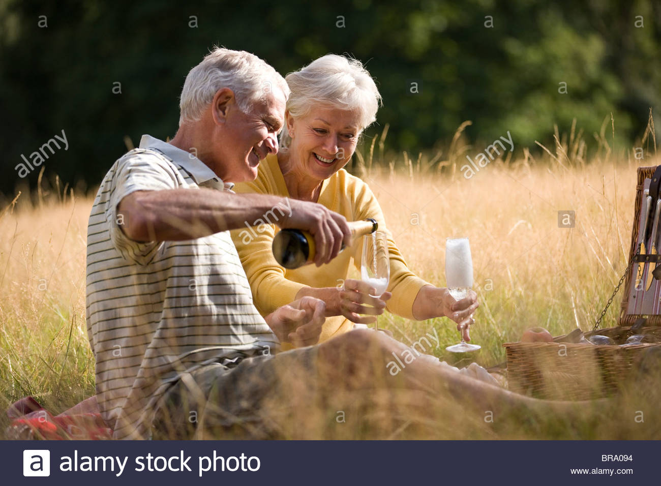 A senior couple having a picnic, man pouring champagne - Stock Image
