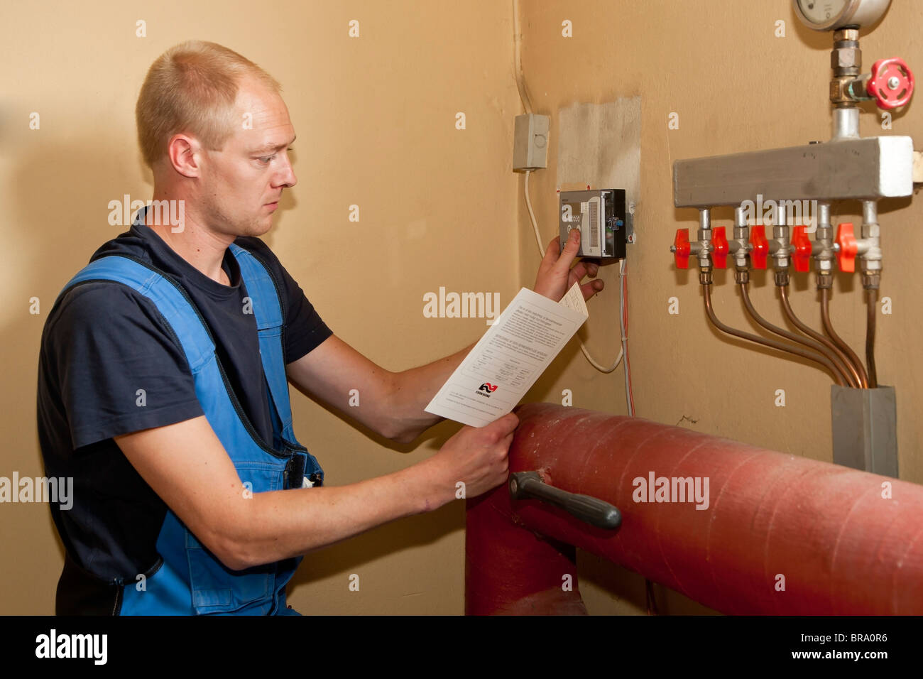 Heating and sanitary technician testing and adjusting the heating controller - Stock Image