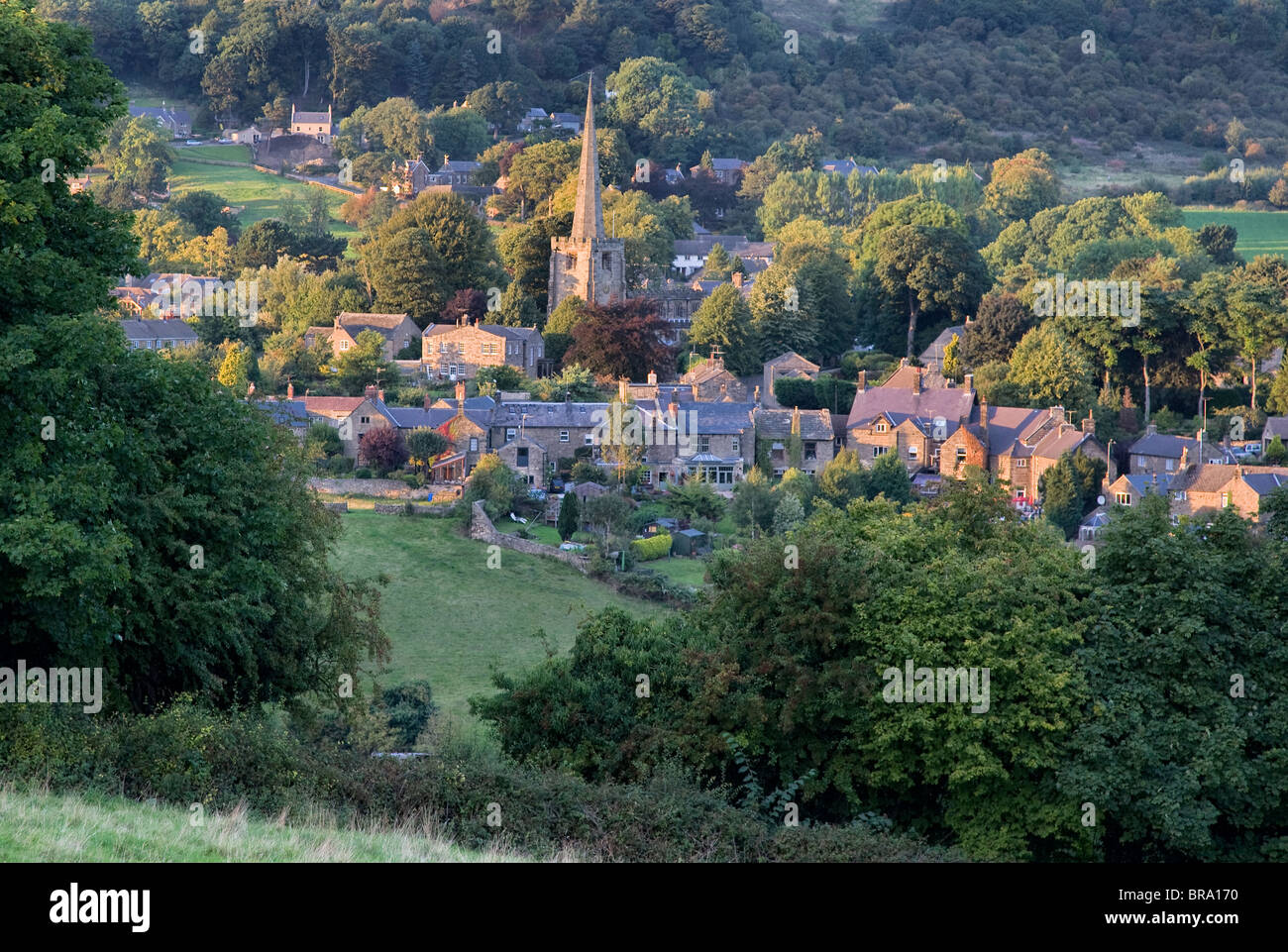 Ashover village Derbyshire and the spire of All Saints parish church in evening light - Stock Image