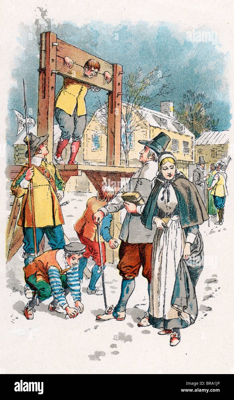 1600s COLONIAL NEW ENGLAND SCENE MAN IN PILLORY BOYS THROWING SNOWBALLS PURITAN COUPLE WALKING WINTER STREET - Stock Image